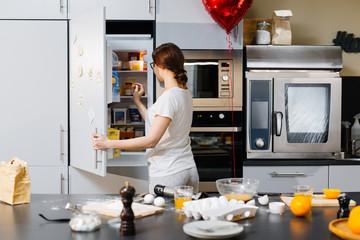 Young woman opening fridge to take something