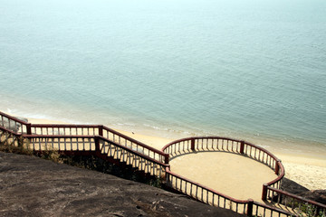 View of a very scenic sea and the beach from the top of the mountain. There is an elegant staircase to go down to the beach with an observation point in between
