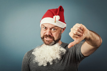 a bearded middle-aged man in a santa hat  giving thumbs down ges