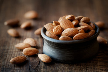 Almonds in a black bowl against dark rustic wooden background