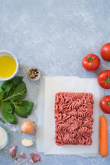 Ingredients for bolognese sauce: ground meat, tomato, carrot, onion, garlic, herbs, seasonings and olive oil