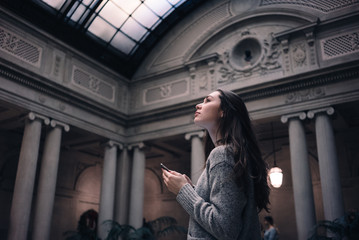 Portrait of a young attractive woman visiting museum or gallery