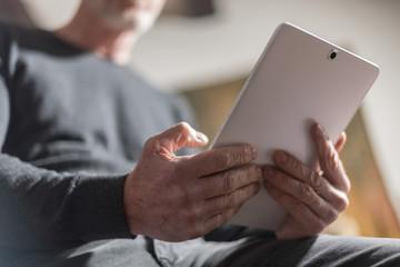 Senior man using his tablet, hard light effect