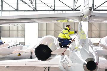 Check of an airplane by a mechanic at the airport in the hangar // Kontrolle eines Flugzeuges durch einen Mechaniker am flughafen im Hangar