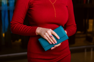 Female hand holding green leather wallet. Fashion and Style