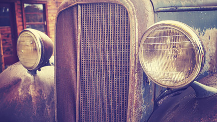 Color toned close up picture of an old rusty car headlamps, selective focus.