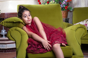 Cute lovlely middle eastern girl with dark red dress and collected hair posing and liying on green sofa at home interior. studio shot.