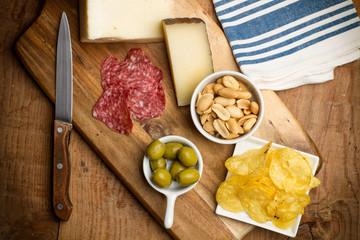 Aperitivo, salchichón, quesos, patatas fritas, olivas sobre tabla de madera rústica. Vista superior