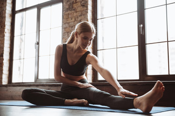 Gorgeous young fitness woman make stretching exercises.