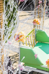 Green bench decorated with yellow roses stands outside in a sunn