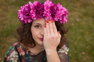 Beautiful curvy girl with a flower crown covering her eye
