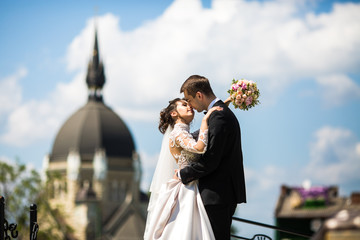 Tender kiss of wedding couple posing before old church