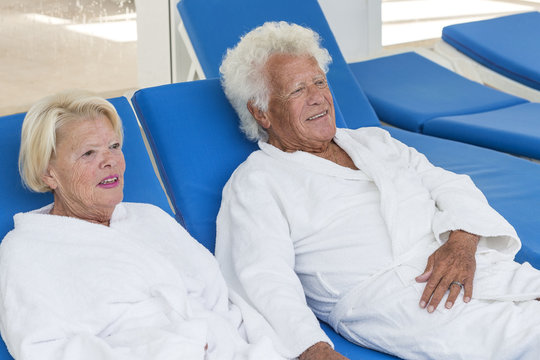 Senior Couple relaxing in spa centre long chairs