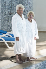 Senior couple in spa with long chair on background