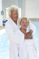 Senior couple in spa with long chair on backgroung