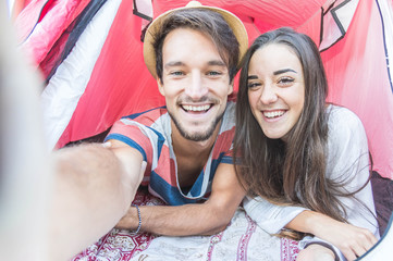 Loving couple taking a selfie in a tent during their journey