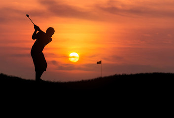 silhouette the boy golfer hit golf ball toward the hole at sunset