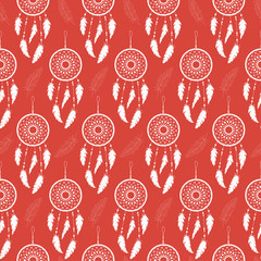 Seamless background of white feathers and dream catchers on a colored background. Pattern.