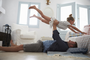 Father Lifting Daughter Into The Air Indoors