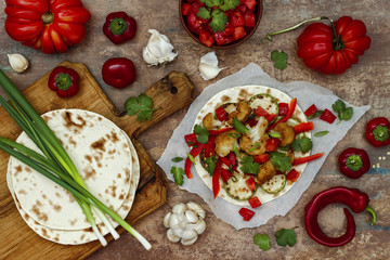 Spicy veggies tacos with roasted cauliflower,  zucchini and tomato salsa on rustic wooden cutting board. Preparing healthy lunch vegetarian snack. Top view, overhead, flat lay
