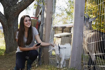 A young woman kneeling down and petting a kid goat through a wire fence.