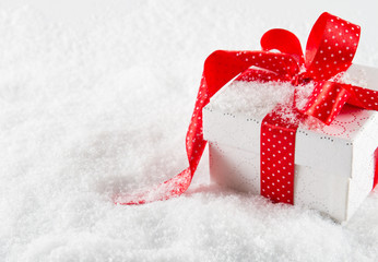 Gift box with red ribbon and bow on snow