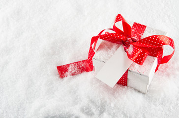 Gift box with red ribbon and bow with note paper on snow