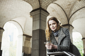 A woman with long hair looking at her smart phone, under an archway.