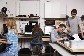 Two women and two men in a technology repair shop or lab, working on computers.