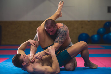 Two mixed martial art fighters grapple in a training room