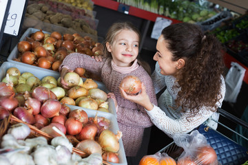 Portrait of mother and little girl purchasing veggies