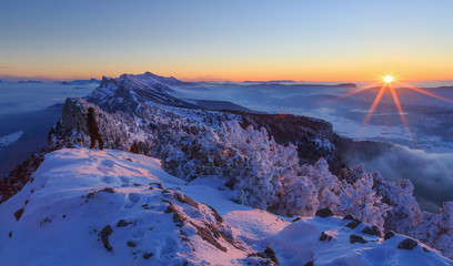 Fotomurales - Hiker looking over a snow covered mountain range, Vercors, France, during a winter sunset.