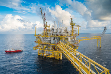 Oil and gas central processing platform in the gulf of Thailand. Construction crane transfer cargo to boat.