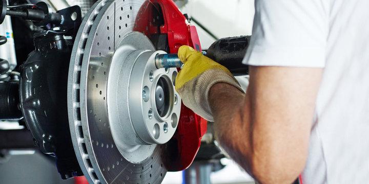 Car mechanic repairs a brake