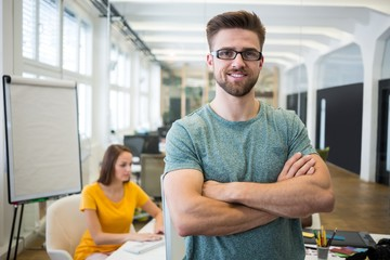 Portrait of smiling graphic designer standing with arms crossed