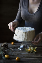 Woman is frosting a chiffon cake