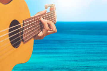 acoustic guitar player on blue sea & skyline background