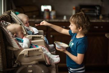 Young boy feeding baby twins