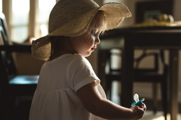 Young girl wearing sun hat staring at dummy