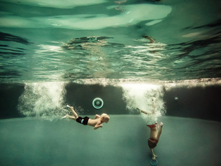 Two boys diving in pool