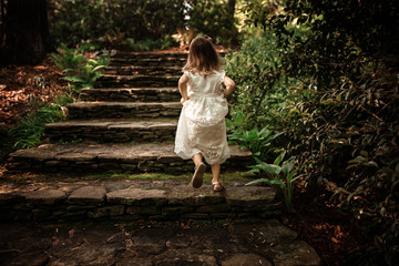 Young girl wearing white dress climbing steps