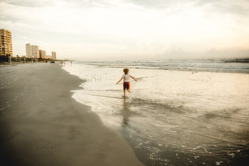 Rear view of boy running on beach