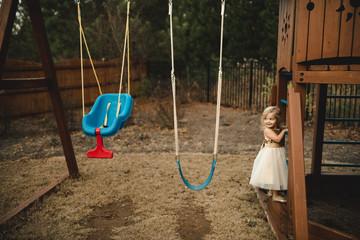 Young girl climbing on frame in garden