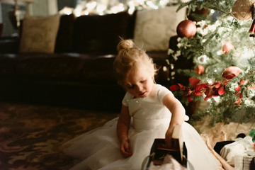Young girl in front of christmas tree wearing white dress