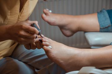 female makes a pedicure. woman has a big ankle