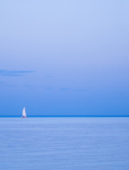 Lonely yacht on horizon. Sailing boat between the sky and sea
