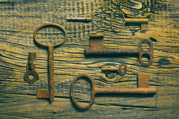 rusty medieval keys on worn out wood table