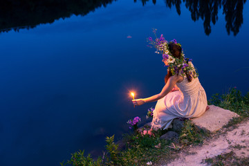 girl in a wreath with a candle sitting by the river