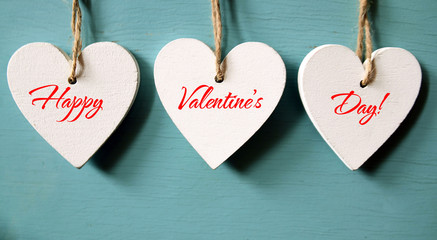 Happy Valentines Day background. Decorative white wooden hearts on a blue wooden background.Selective focus.St.Valentine's Day concept.