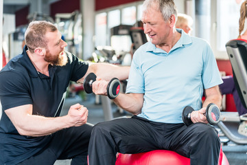 senior man working out with personal trainer at the gym